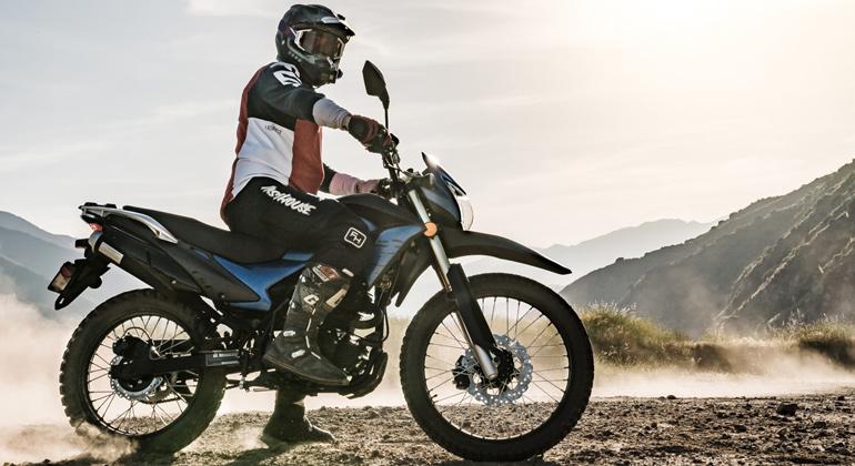 На картинке находится стоящий мотоцикл Эндуро с мотоциклистом на верху. На фото хорошо видно, что у мотоцикла высокая посадка