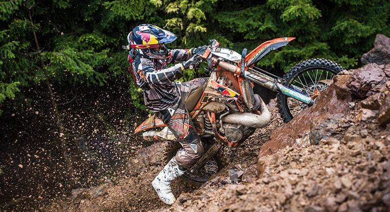 На картинке изображён мотоцеклист вверхом на эндуро, который поднимается сквозь грязь по холму